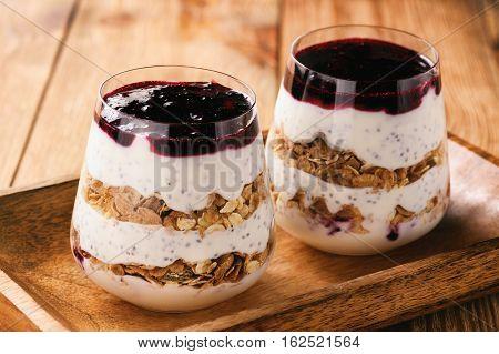 Yogurt dessert with chia seeds, muesli and black currant jam.