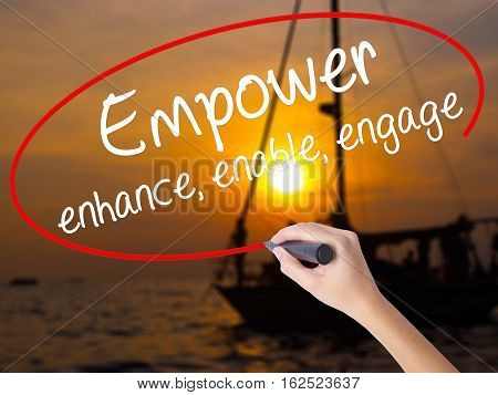 Woman Hand Writing Empower Enhance, Enable, Engage With A Marker Over Transparent Board