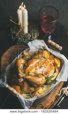Christmas holiday table set with roasted whole chicken stuffed with oranges, bulgur and rosemary, decorative candles and glass of rose wine, grey wall background. Selective focus, Slow food concept