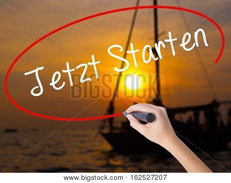 Woman Hand Writing Jetzt Starten (start Now In German) With A Marker Over Transparent Board