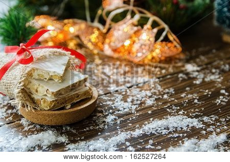 Turron traditional Spanish sweet for Christmas. Almond nougat dessert served in cork plate on dark background with snow and Christmas tree with garland.Copy space