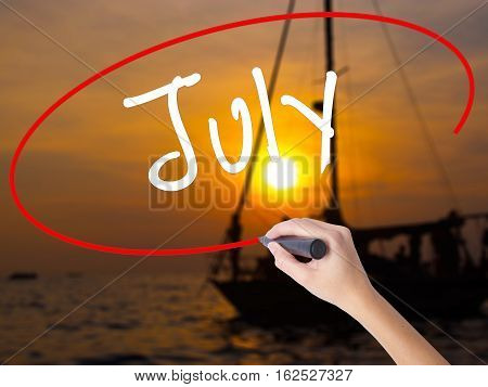 Woman Hand Writing July With A Marker Over Transparent Board