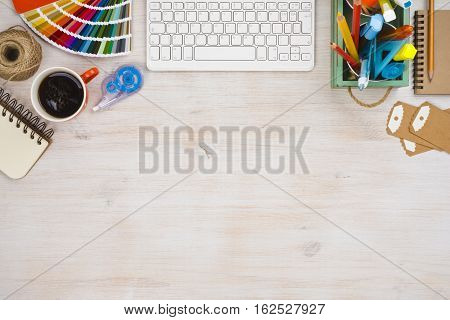 Designer workspace top view with essential elements on wooden board