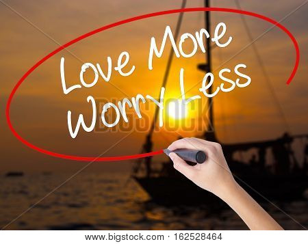 Woman Hand Writing Love More Worry Less With A Marker Over Transparent Board.