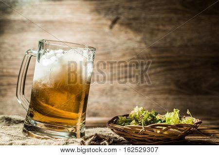 Foamy beer poured from cup standing on linen cloth on wooden table