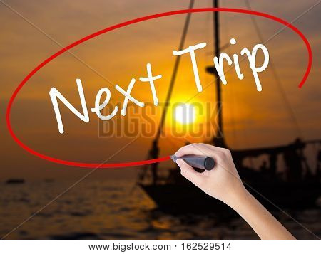 Woman Hand Writing Next Trip With A Marker Over Transparent Board