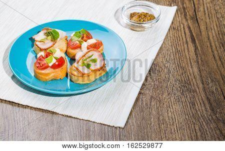 Traditional Italian antipasti bruschetta with tomato, cheese and bacon