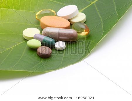 Vitamine, Tabletten und Pillen auf grünes Blatt