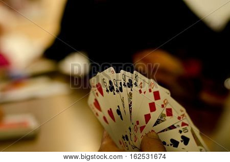rom poker playing cards in his hands during a game between friends