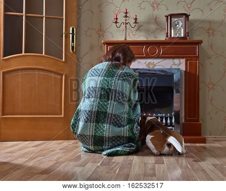 woman in the blanket with dog near a fireplace