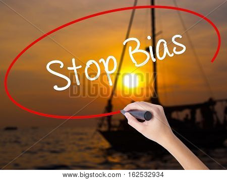 Woman Hand Writing Stop Bias With A Marker Over Transparent Board