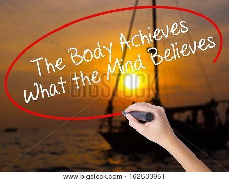 Woman Hand Writing The Body Achieves What The Mind Believes With A Marker Over Transparent Board