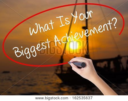 Woman Hand Writing What Is Your Biggest Achievement? With A Marker Over Transparent Board