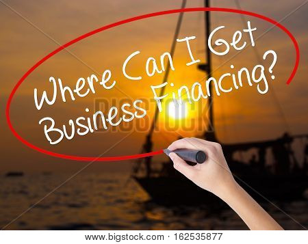 Woman Hand Writing Where Can I Get Business Financing? With A Marker Over Transparent Board.