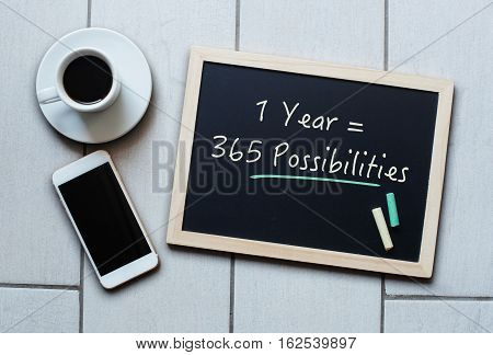 Chalkboard or Blackboard concept saying - 1 Year = 365 Possibilities - with coffee and mobile phone. Business Education Effective Inspiration Personal Motivation Management concept.