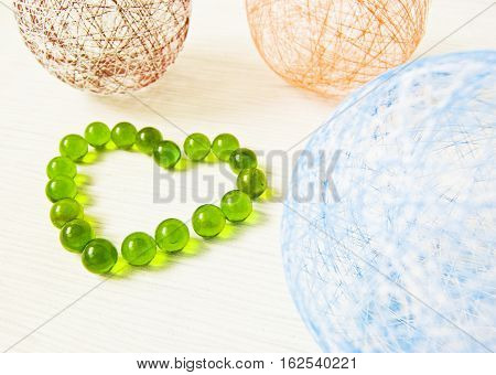 balls of yarn of different colors on a light background heart of green glass beads