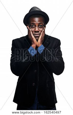 The portrait of handsome young black african unhappy man in hat on white background. Negative human emotions and power demonstration