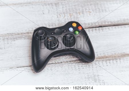 Wireless black gamepad or game controller for console gaming on white wooden background