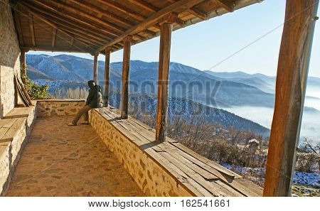 The old stone terrace with the wooden pillars overlooks the misty mountains around Kastoria Greece.