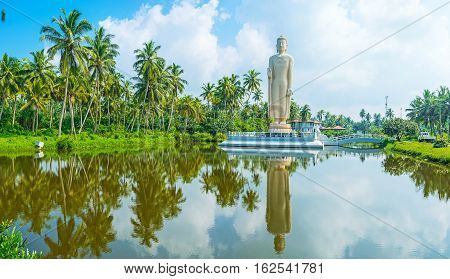 Tsunami Honganji Viharaya is the giant Buddha Statue dedicated to Tsunami victims located on the tiny island and surrounded by lush palm garden in Peraliya Sri Lanka.