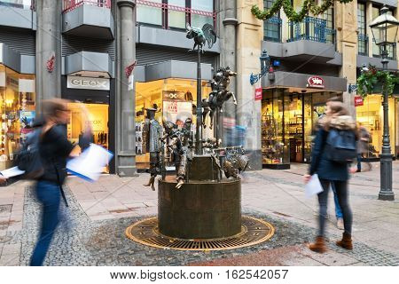 AACHEN, NORDRHEIN-WESTFALEN/GERMANY -  NOVEMBER 22, 2016: Busy street with shops and a fountain decorated for Christmas  in the city center