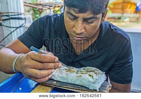MEETIYAGODA SRI LANKA - DECEMBER 5 2016: The silversmith lat his work producing the jewelry base on December 5 in Meetiyagoda.