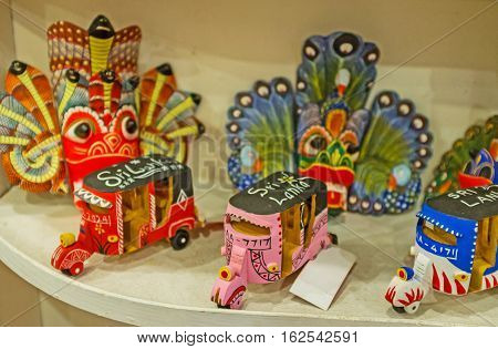 AMBALANGODA SRI LANKA - DECEMBER 5 2016: The small wooden tuk tuks among masks and other souvenirs in tourist store on December 5 in Ambalangoda.