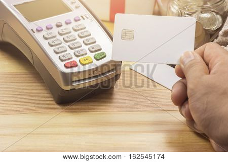 Cashier Hand Holding A Credit Card Over Edc Machine Or Credit Card Terminal With Calculator And Gift