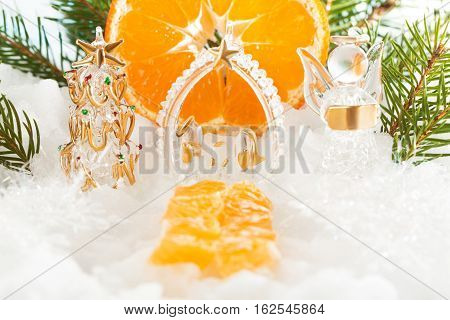 Catholic Christmas composition. The trail leading to the Christmas tree, the birth of Christ and the angel of new year decorations, mandarin sun