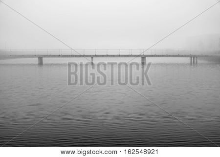 Mysterious scene with bridge crossing a river in a foggy and misty landscape black and white