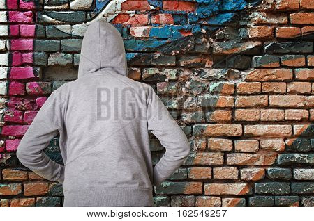 Rear view of hooded man against wall with graffiti