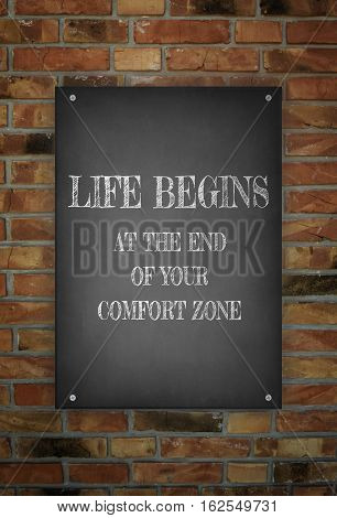 LIFE BEGINS AT THE END OF YOUR COMFORT ZONE hand drawn poster on brick wall
