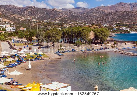 Agios Nikolaos, Greece - August 2, 2012: Tourists Swim In The Mediterranean Sea On The Beach