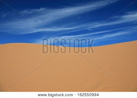 Red sand dunes on the background of blue sky with clouds in Mui Ne Vietnam