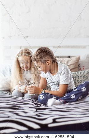 girl and boy sitting in pajamas on the bed and drink milk from a glass cup