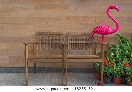 Two wooden chair in the garden wood background .