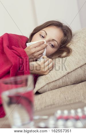 Sick woman covered with a blanket lying in bed with high fever and a flu blowing her nose. Pills and glass of water on the table