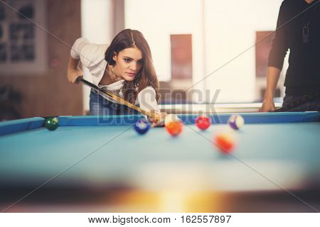 Young beautiful young woman aiming to take the snooker shot while leaning over the table in a club