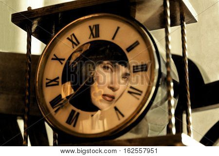 Reflection of the girl in the old clock