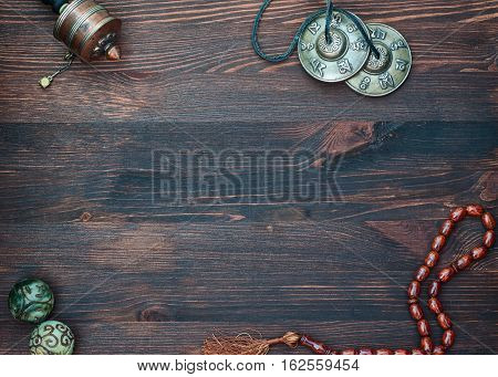 Prayer wheel prayer beads magic balls and brass plates for religious ritual a top view an empty space in the middle