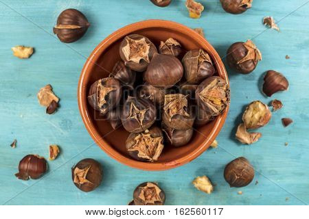 An overhead photo of peeled and unpeeled roasted chestnuts in an earthenware bowl, on a vibrant teal blue background