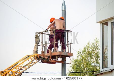 Two electricians working with naked torso. Repair street light electricity post. Bucket and arm boom lift