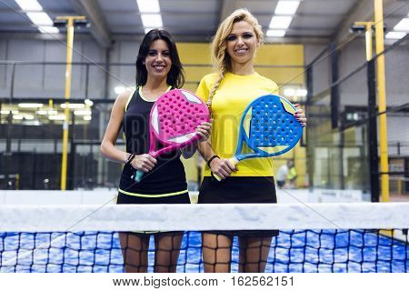 Two Beautiful Young Women Posing On Paddle Tennis Court.