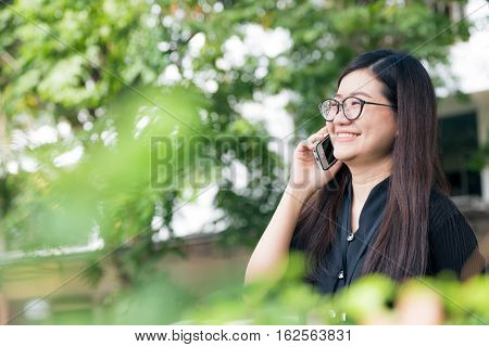 Happy Asian Glasses Woman Use To Talking On Smart Phone Outdoor