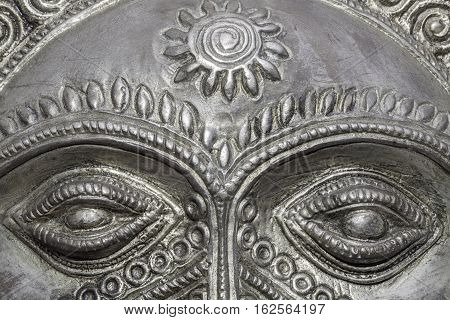 Big Brother is watching you. Close up of the eyes on a traditional ornate silver Sun God mask. Symbolic of omnicient powers watching over us.