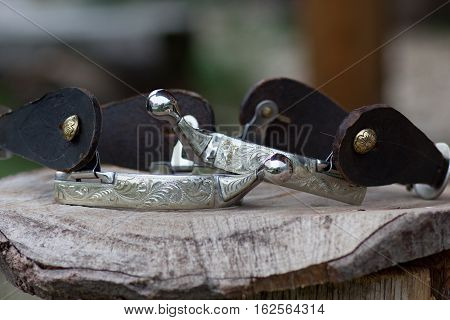 cowboy silver spurs with engraving on the wooden mat