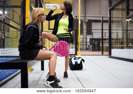 Two Young Women Relaxing After The Paddle Tennis Match.