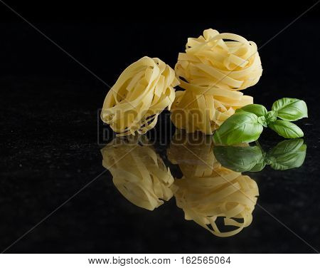 Pasta Tagliatelle Arranged On Marble Table. Raw Closeup Background. Delicious Dry Uncooked Ingredien