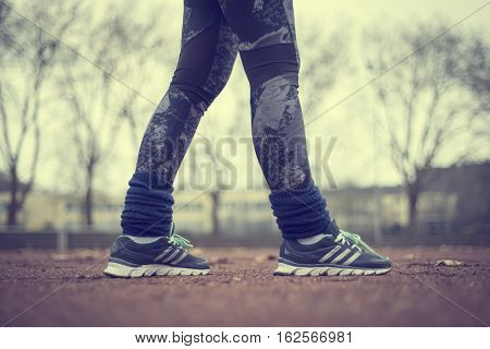 Runner legs on red running track at stadium or sports field.