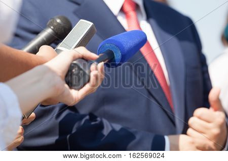 Media interview with businessman, politician or spokesperson. Press conference.